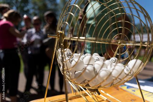 Fotografía Bingo balls on a table next to a lotto raffle drum machine