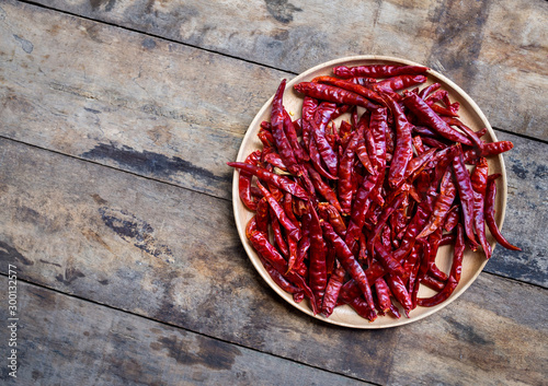 Foto op Aluminium Hot chili peppers Red hot dry chili peppers in wooden bowl on wood background, top view