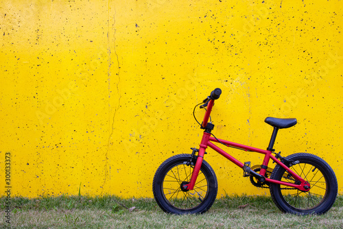 Photo 壁に立てかけられた赤い自転車