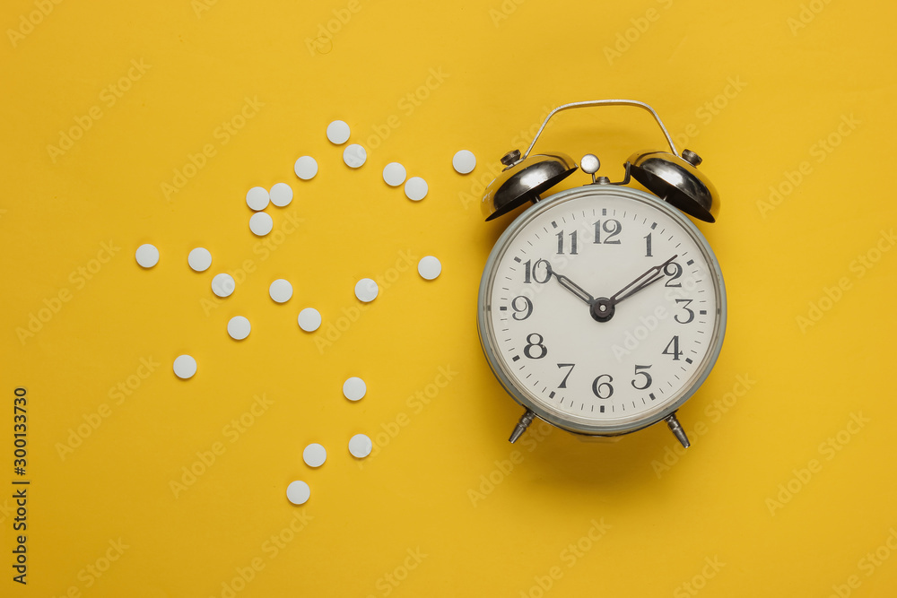 Fototapety, obrazy: Time to take pills. Pills and alarm clock on yellow background. Top view