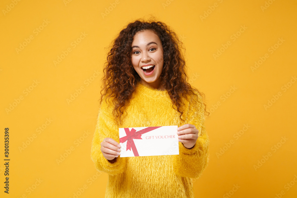 Fototapety, obrazy: Excited young african american girl in fur sweater posing isolated on yellow orange background studio portrait. People lifestyle concept. Mock up copy space. Hold gift certificate, keeping mouth open.