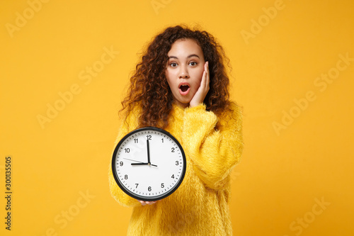 Shocked young african american girl in fur sweater posing isolated on yellow orange background, studio portrait. People lifestyle concept. Mock up copy space. Holding clock, putting hand on cheek.