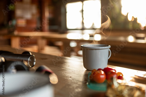 Grey enamel cup of hot steaming coffee or tea sitting on an old table in a mountain shelter.