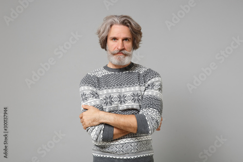 Handsome elderly gray-haired mustache bearded man in knitted sweater posing isolated on grey wall background, studio portrait Tablou Canvas