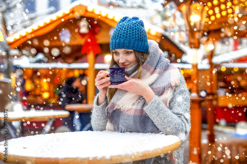 Beautiful young woman drinking hot punch, mulled wine on Christmas market. Happy girl in winter clothes with lights on background on winter snow day in Vienna, Austria.