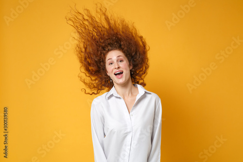 Vászonkép  Excited young redhead woman girl in white shirt posing isolated on yellow orange wall background