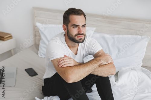Calm young handsome bearded man sitting in bed with white sheet pillow blanket in bedroom at home Tablou Canvas