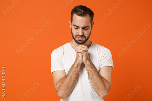 Obraz na plátne  Upset young man in casual white t-shirt posing isolated on bright orange wall background studio portrait