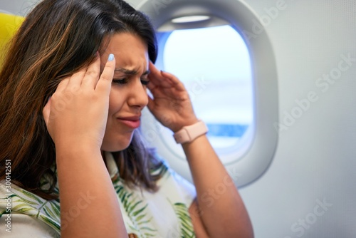 Young traveller woman sitting inside plane at the airport with sky view from the Wallpaper Mural
