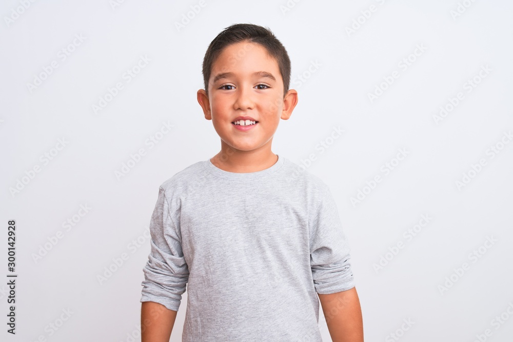 Obraz Beautiful kid boy wearing grey casual t-shirt standing over isolated white background with a happy and cool smile on face. Lucky person. fototapeta, plakat