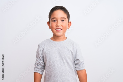 Beautiful kid boy wearing grey casual t-shirt standing over isolated white background with a happy and cool smile on face. Lucky person.