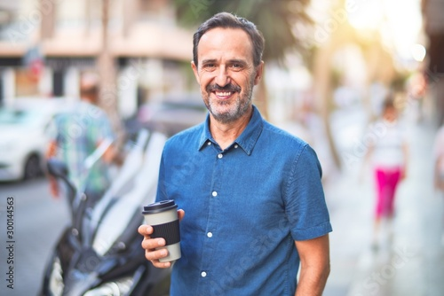Fototapety, obrazy: Middle age handsome man standing on the street drinking take away coffee smiling