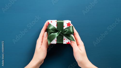 Valokuva  Small Christmas present with green ribbon bow in woman hands
