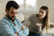 Angry man doesn't pay attention to his girlfriend who is asking for his forgiveness