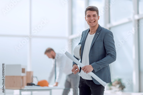 smiling architect standing in a bright office. Wallpaper Mural