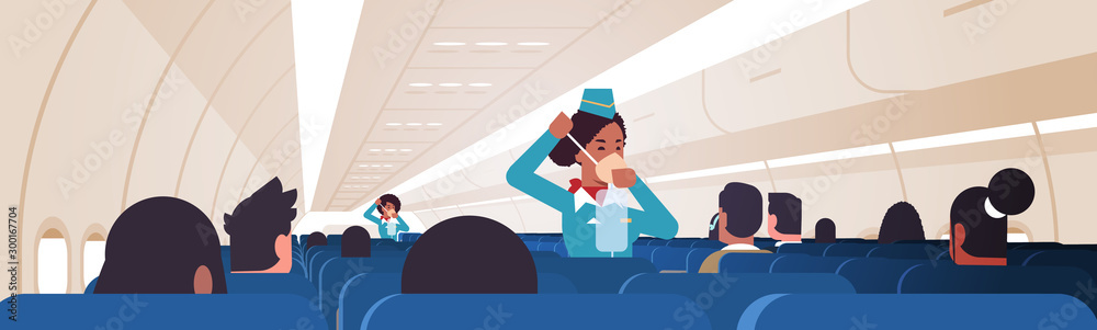 Fototapety, obrazy: stewardess explaining for passengers how to use oxygen mask in emergency situation african american flight attendants safety demonstration concept modern airplane board interior horizontal vector