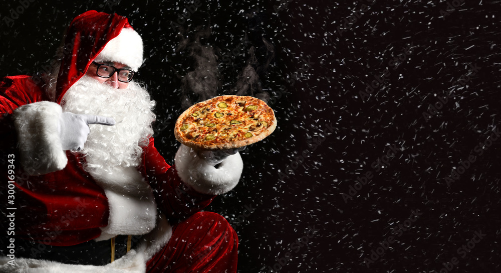 Fototapeta Happy laughing Santa Claus hold big hot steaming original pizza offering pointing finger. New year and Xmas fast food