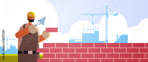 Cuadros en Lienzo male builder using spatula workman laying brick wall worker in uniform bricklayi
