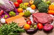 Trending paleo/pegan diet. Healthy balanced food concept. Set of fresh products, raw meat, salmon, vegetables and fruits