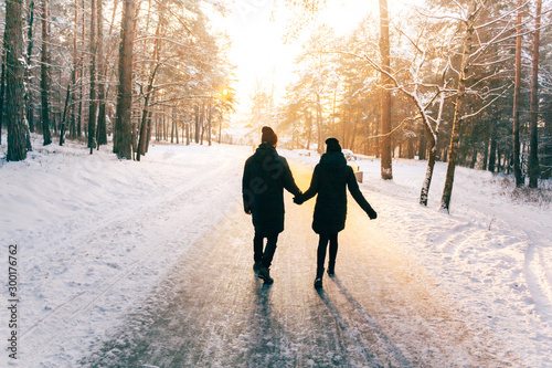 Couple Holding Hands Walking Away. Winter, Sunny, Forrest, Recreation, Leisure, Clothing.