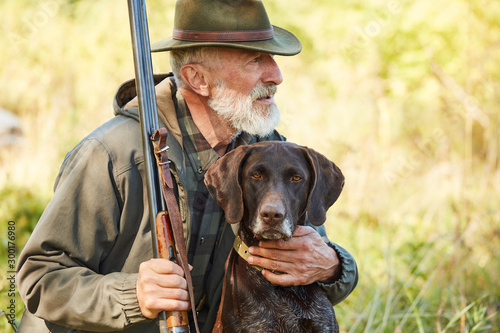 Caucasian mature man with gun and dog sit searching prey Tableau sur Toile