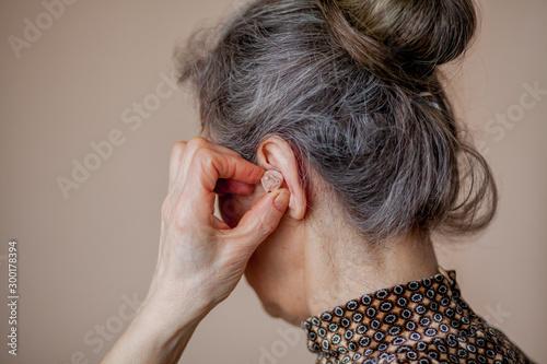Fotografie, Tablou  closeup senior woman inserting hearing aid in her ears