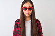 Leinwandbild Motiv Young chinese woman wearing casual jacket and sunglasses over isolated white background with a confident expression on smart face thinking serious