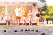 Friends Playing Petanque Guy Through A Ball Above Summer Cafe Outdoor Activity Sunset Light