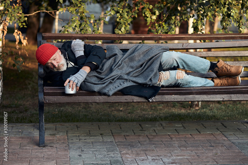 Fotomural Vagrant male lying on street bench asking for money, for any help