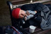 Penniless Senior Man Lying On Park Bench, Trembling From The Cold. Cup For Collecting Money, Coins Next To Him.