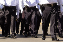 Close Up Of  Police Males, Wearing Dark Blue Pants And White Shirt At A Parade