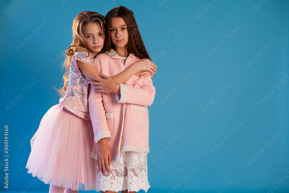 Photo  Two beautiful fashionable girl girlfriends in pink and white dresses