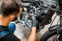 Worker Repairing Motorcycle Engine At The Workshop