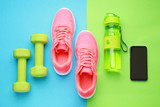 Sports water bottle, shoes, mobile phone and dumbbells on color background