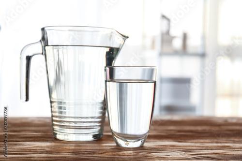 Fototapeta Glass and jug of fresh water on table in room obraz