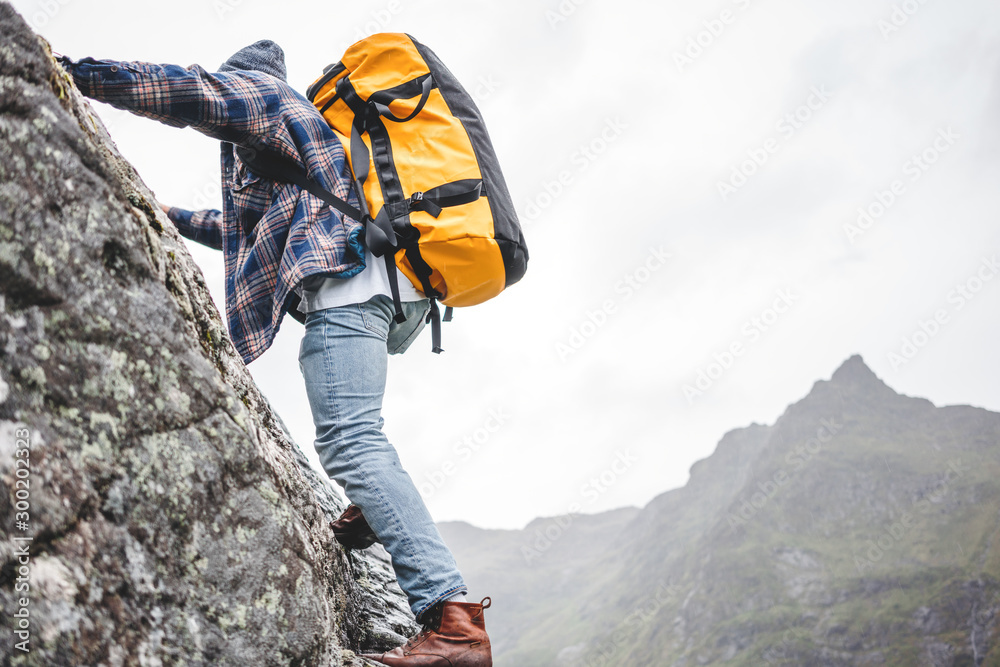Fototapety, obrazy: Brave lifestyle climber with professional backpack climb to the rock. Active fearless tourist swarm up on mountain