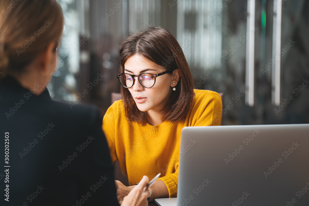 Fototapeta Team of young business woman have meeting in modern office. Two female manager using laptop at workplace at office