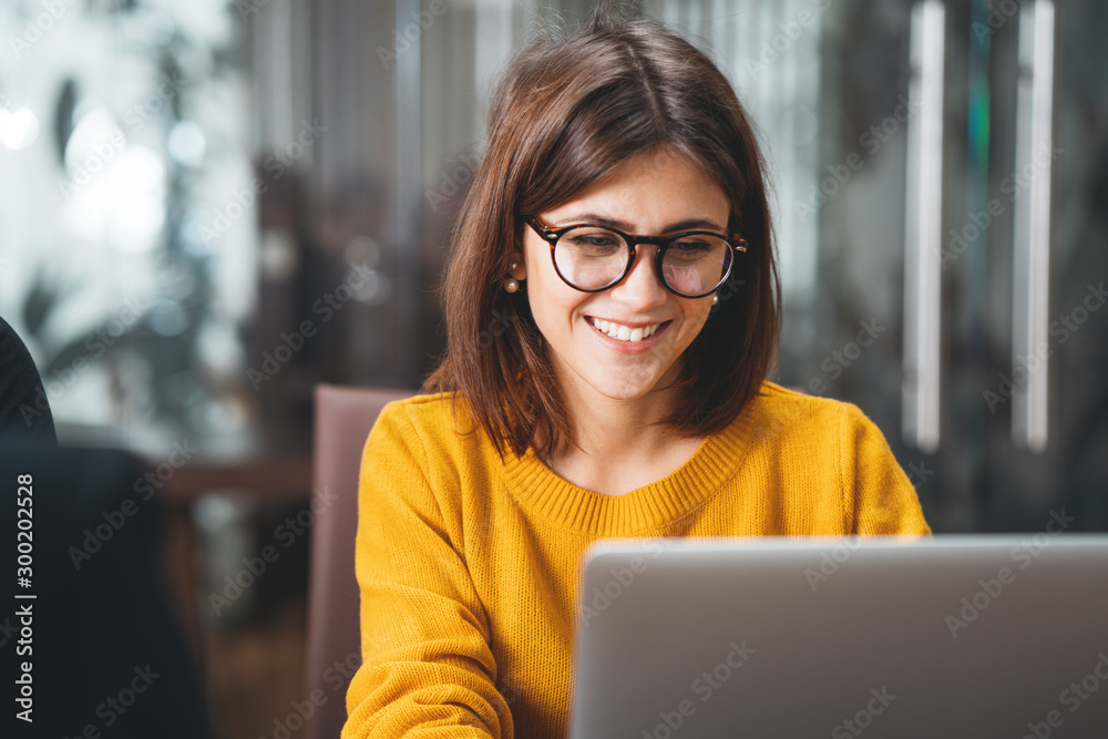 Fototapeta Portrait of happy business woman wearing glasses at workplace in office. Young handsome female worker using modern laptop