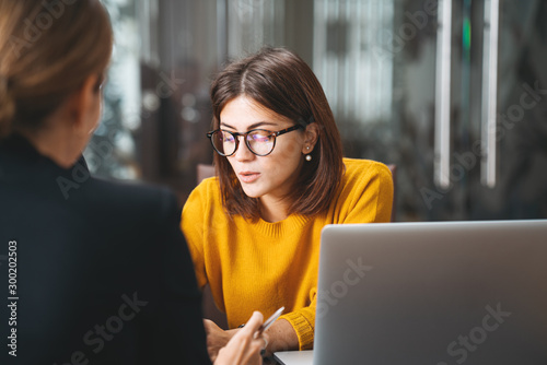 Obraz Team of young business woman have meeting in modern office. Two female manager using laptop at workplace at office - fototapety do salonu