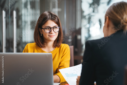 Fototapeta Group of happy business people have meeting at workplace in office. Two positive woman working together using modern laptop for working concept obraz