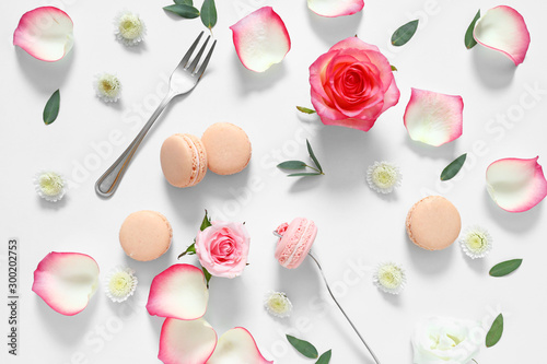 Fotobehang Macarons Tasty macarons with rose flowers on white background