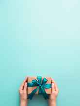 Female Hands Hold Gift Box On Turquoise Blue Background, Copy Space. Caucasian Girl Hands Holding Gift Box In Craft Wrapping Paper With Green Satin Ribbon. Christmas, New Year Or Birthday Present
