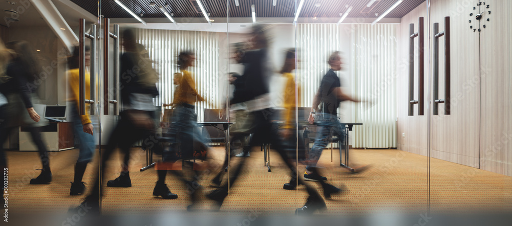 Fototapeta Businesspeople walking at modern office. Group of business employees at coworking center. Motion blur. Concept work process. Wide image