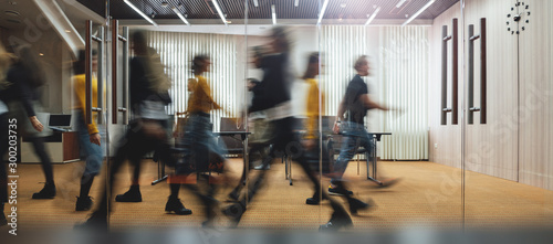 Obraz Businesspeople walking at modern office. Group of business employees at coworking center. Motion blur. Concept work process. Wide image - fototapety do salonu