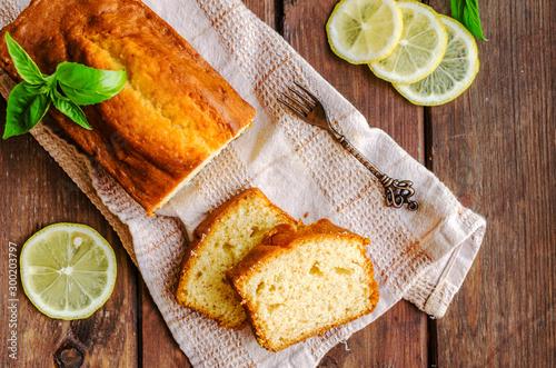 Fotografie, Tablou Lemon pound cake on rustic wooden background with lemon.