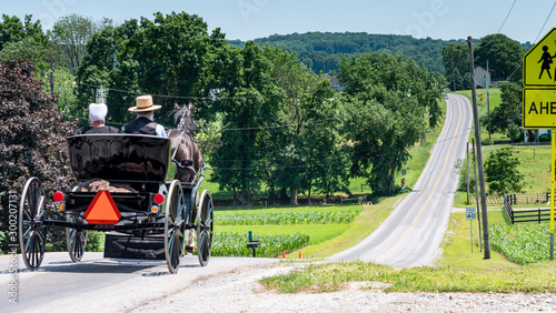 Photo Amish Open Horse and Buggy with 2 Amish Adults in it trotting down the Hill on a