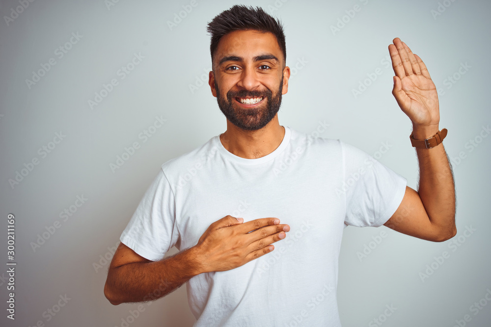Fototapeta Young indian man wearing t-shirt standing over isolated white background smiling swearing with hand on chest and fingers up, making a loyalty promise oath