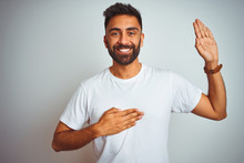 Young Indian Man Wearing T-shirt Standing Over Isolated White Background Smiling Swearing With Hand On Chest And Fingers Up, Making A Loyalty Promise Oath