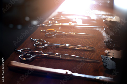 scissors, razor, trimmer and nozzles lie on a wooden table, a set of barber equipment, hairdresser tools
