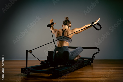Fototapeta Young girl doing pilates exercises with a reformer bed. Beautiful slim fitness trainer on reformer gray background, low key, art light. Fitness concept obraz